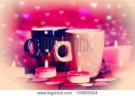 Two cups and candles on table on bright lights background