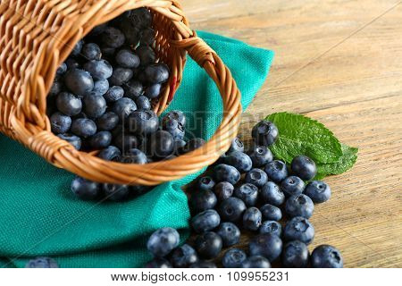 Tasty ripe blueberries with green leaves in basket on wooden table close up