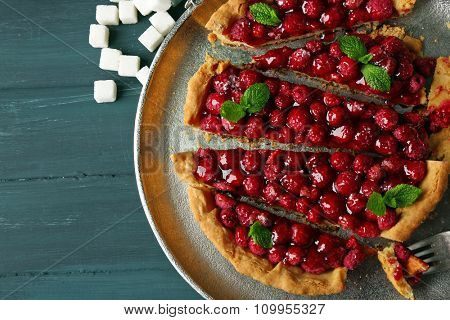 Tart with raspberries on tray, on wooden background