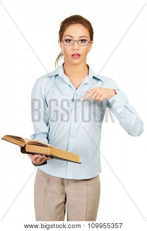Shocked business woman holding a book.