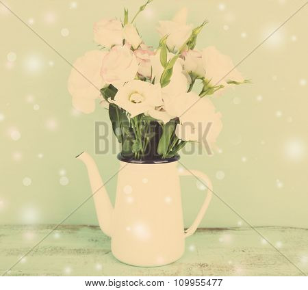 Beautiful eustoma flowers in teapot, on color background