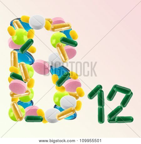 B 12 made of different pills on colour background