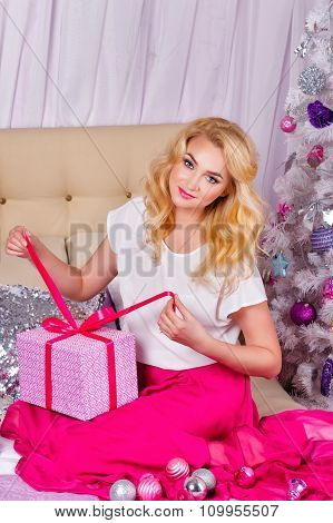 Girl Sitting On The Couch And Unpacks Christmas Gifts.
