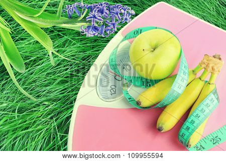 Fruits on scales on green grass.  Losing weight for the summer