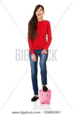 Happy student woman with piggybank under leg.