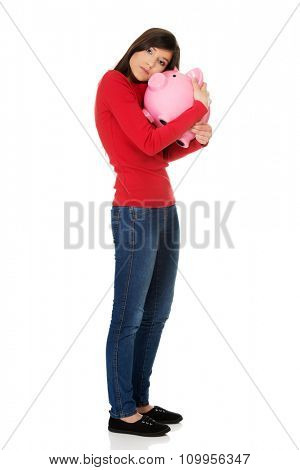 Happy young student woman with piggybank.