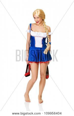 Oktoberfest woman in Bavarian dress holding her shoes.