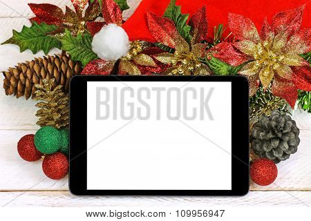 A black tablet computer with blank white screen on top of glittery Christmas decoration on white wooden background