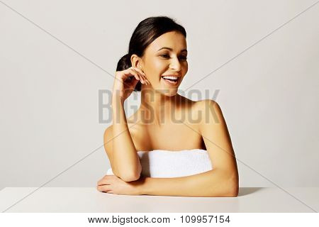 Slim spa woman standing near desk with rolled towel