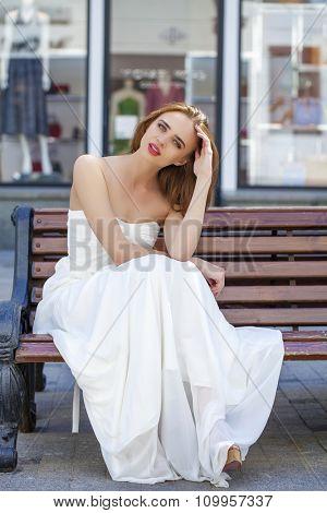 Full length portrait of beautiful model woman in wearing white dress posing summer street