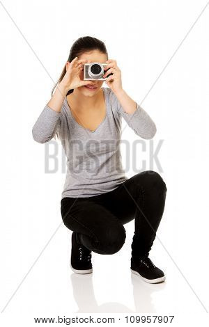 Teen woman taking a photo with a camera.