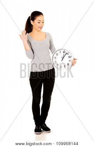 Young shocked woman with a clock.