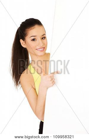 Fitness woman pointing on white empty banner.