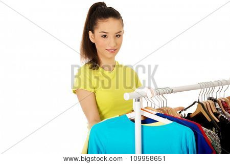 Smiling young woman thinking what to dress.