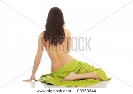 Beautiful woman in towel sitting on the floor.