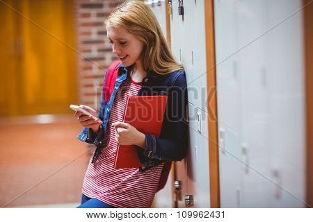 Smiling student leaning against the locker using smartphone at the university