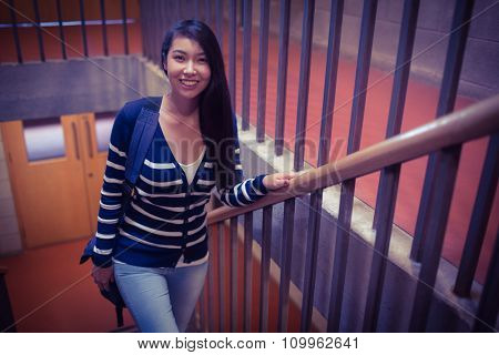 Smiling student walking up steps at the university