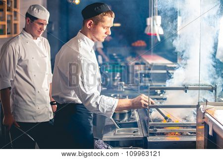 young male cooks preparing meal on the grill