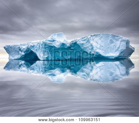 Big glacier in the snow with reslection in water