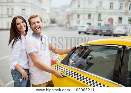 Smiling coung couple with taxi