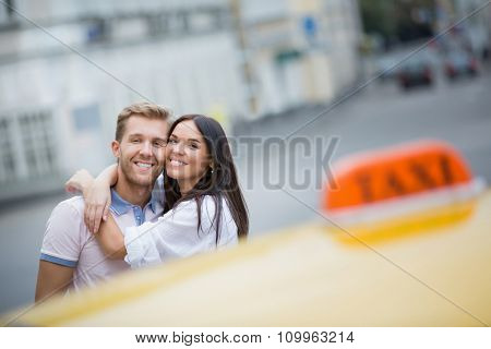 Smiling young couple with taxi