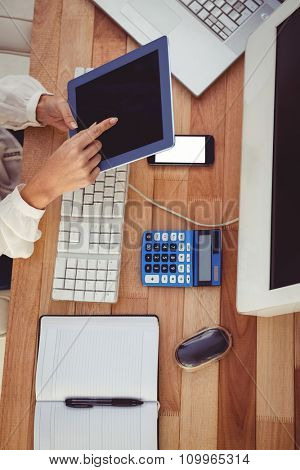 Cropped image of woman using tablet in her office