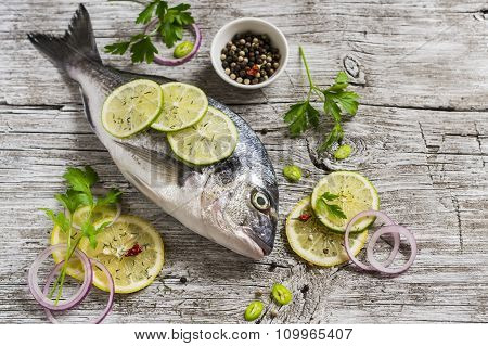 Raw Ingredients - Fresh Dorado Fish, Lemon, Lime And Parsley On A Light Rustic Wooden Surface