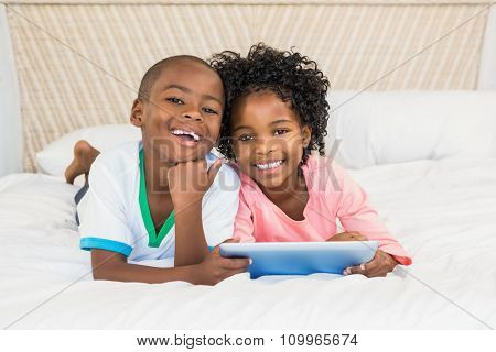 Happy siblings using tablet on bed at home