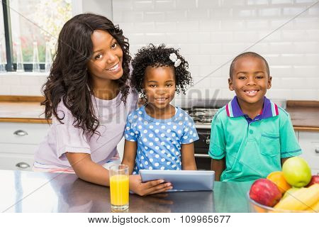Mother and children using tablet in the kitchen