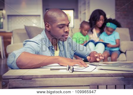 Man with bills and calculator in living room