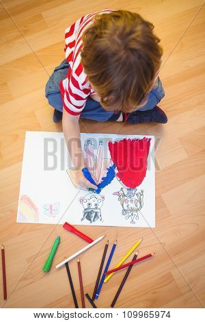 Small boy drawing on paper on the floor