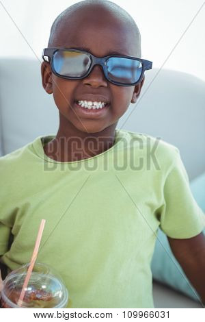 Smiling boy wearing 3d glasses for a movie on the couch