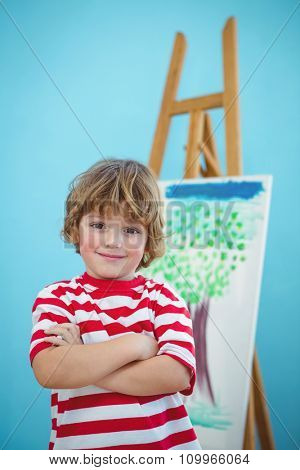 Happy boy with folded arms beside an easel