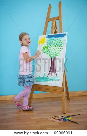 Smiling girl beside her picture on an easel