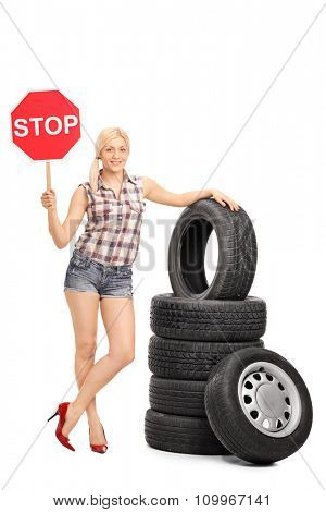 Full length portrait of a young female mechanic posing next to a stack of tires and holding a stop sign isolated on white background
