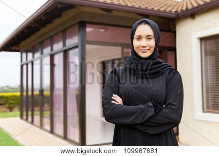 beautiful middle eastern woman standing in front of her house