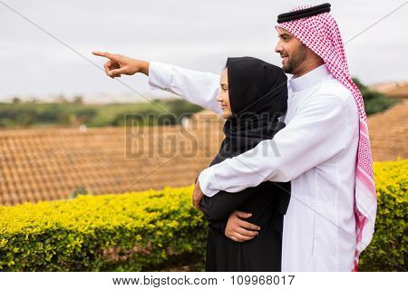 cheerful young middle eastern couple pointing outside their house