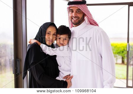 portrait of happy young muslim family of three standing together