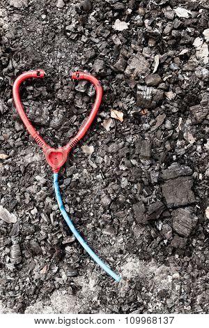 Plastic toy stethoscope on burned ground