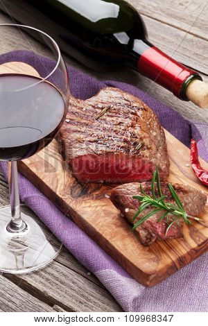 Grilled beef steak and red wine on wooden table