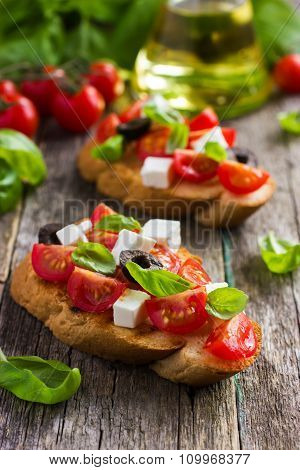 Bruschetta With Tomato, Feta Cheese, Olives And Basil