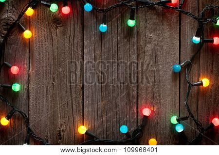 Christmas colorful lights frame on wooden table with copy space
