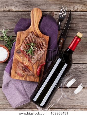 Grilled beef steak with rosemary, salt and pepper and wine bottle on wooden table. Top view