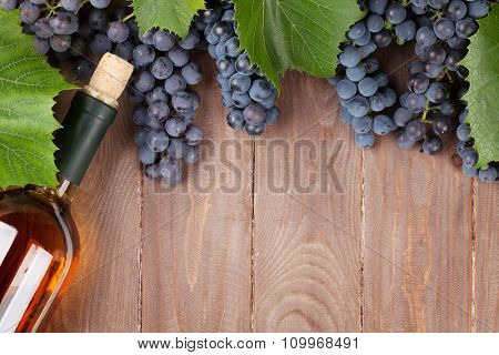 Red grape and wine bottle on wooden table. Top view with copy space
