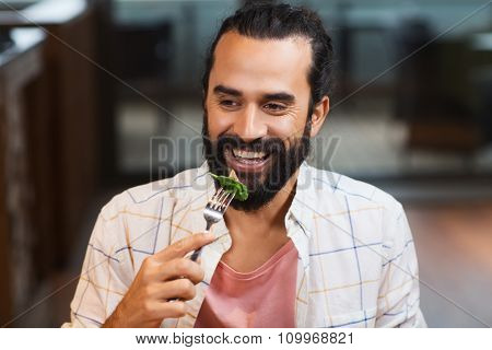 leisure, food, eating, people and holidays concept - happy man with friends having dinner at restaurant