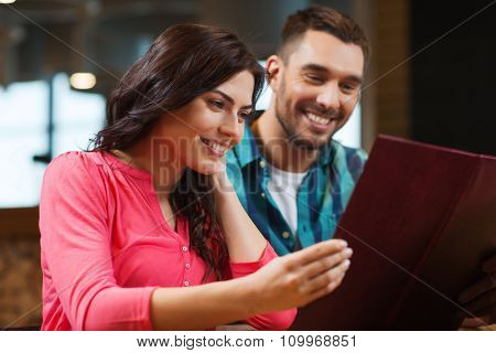 leisure, people and holidays concept - smiling couple with menus at restaurant