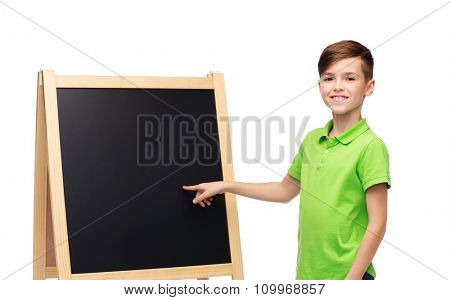 childhood, education, school, advertisement and people concept - happy smiling boy in green polo t-shirt with chalk and blank school blackboard