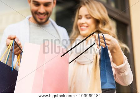 sale, consumerism and people concept - close up of happy couple looking into shopping bag at shop window on city street