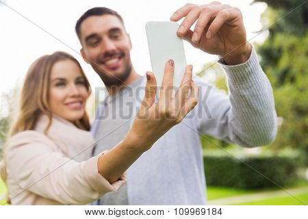 love, relationship, technology and people concept - close up of happy couple with smartphone taking selfie in summer park