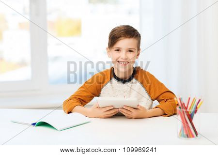 leisure, children, education, technology and people concept - smiling boy with tablet pc computer and notebook at home